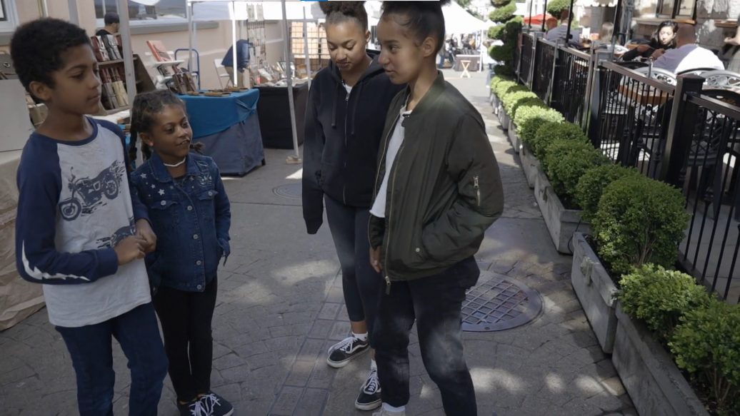 4 children-youth standing in public square
